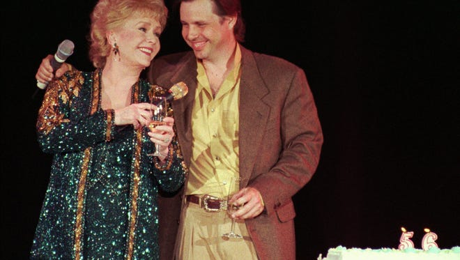 "FILE - In this April 1, 1997, file photo, Debbie Reynolds, left, celebrates her 65th birthday on stage as her son, Todd Fisher, presents her with a cake following her evening variety show, at the Debbie Reynolds Hotel in Las Vegas. Fisher told Entertainment Tonight for an interview published online on March 22, 2017, that Reynolds set him up ""for her leaving the planet"" the day his sister and Reynolds' daughter Carrie Fisher died in December 2016. (AP Photo/Lennox McLendon, File)"