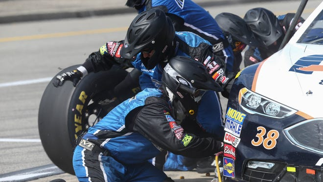Landon Cassill's pit crew change tires on the No. 38 Ford at Michigan International Speedway.