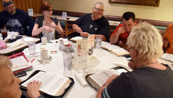 Pastor Rex Wiseman guides a Bible Study with members of the Lost & Found Outreach Ministry.  The ministry is located next to the 49 Flea Market.