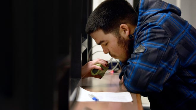 As part of the 24/7 Sobriety Program, Gage Peck takes a Breathalyzer test at the Minnehaha County Jail in Sioux Falls, S.D. on Thursday, Dec. 1, 2016. The program requires offenders who face drunken driving charges to stop by the jail twice a day to take a Breathalyzer test.