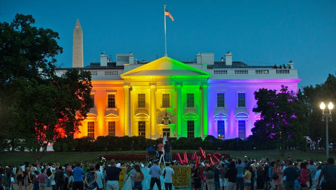 People gather in Lafayette Park to see the White House illuminated with rainbow colors in commemoration of the Supreme Court's ruling to legalize same-sex marriage on June 26, 2015.