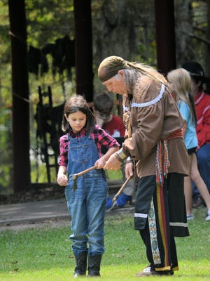 """Chief John """"Sitting Bear"""" Mayeux demonstrating tomahawk throwing at last year's Native American Culture Day."""