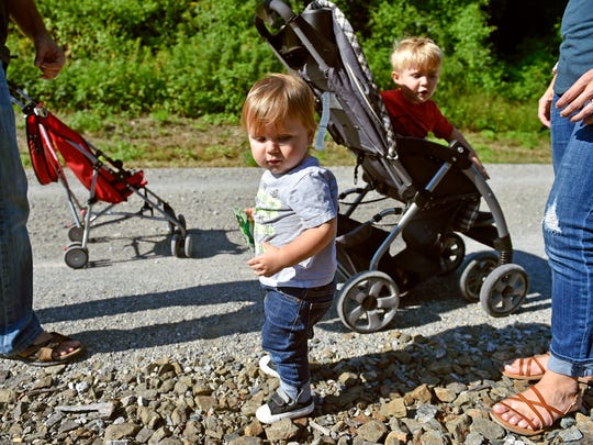 """Jack Nevin, 1, looks for a place to leave a decorated rock as father Roo, left; brother Phillip, 3; and mother Gretchen, right, watch on the York County Rail Trail near Glen Rock Saturday, Sept. 16, 2017. Gretchen Nevin began decorating small rocks and leaving them on the York County Heritage Rail Trail for others to find and keep or re-hide, as an up-and-coming trend of """"painted rocks"""" that encourages people to enjoy the outdoors and see what rocks they can find. Nevin decorates several rocks daily and walks the rail trail weekly with her family to leave the rocks at various points."""
