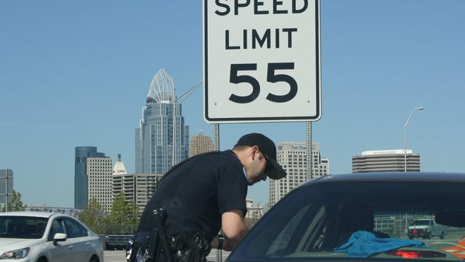 Fort Thomas Police Department officer Derek Faught questions a motorist on north I-471 within sight of Cincinnati. The driver did not have heroin and was issued a warning for not wearing a seat belt.