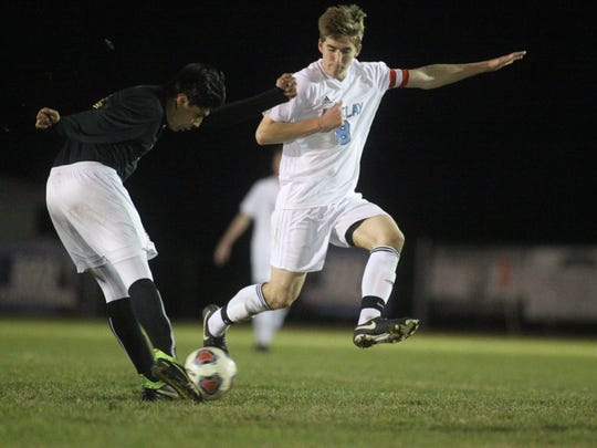 Florida High's Danny Perez plays a ball forward as Maclay's Daniel Sweeney tries to block it.
