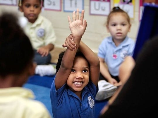 April 6, 2015 -  Carmen Worles tries to catch the attention of her pre-K teacher, Sia Krog, to answer a question Monday morning at St Augustine Catholic School, part of the Jubilee Schools network.  (Jim Weber/The Commercial Appeal)