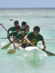 In this May 20, 2017, file photo, the John F. Kennedy Islanders Manhoben Lalahi team pushes for the finish during their Independent Interscholastic Association of Guam and the Guam Kayak and Canoe Federation Paddling Series 500-meter race at Matapang Beach.