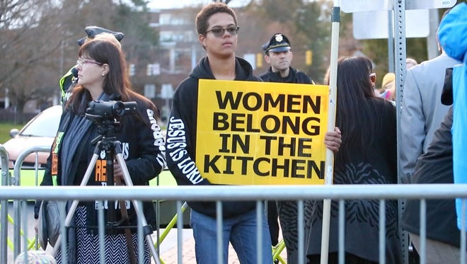 "A member of the Key of David Christian Center holds a sign reading ""Women Belong In The Kitchen"" Wednesday at the University of Delaware. The group was met with the voices of many UD students opposing their message and beliefs."