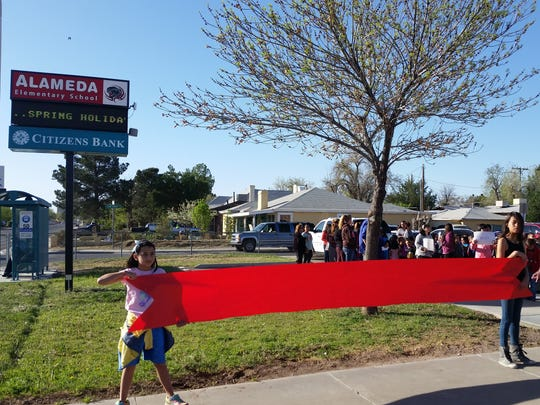 Students at Alameda Elementary hold a red paper ribbon ahead of Wednesday morning's ribbon-cutting to unveil a new digital marquee donated by Citizens Bank of Las Cruces.