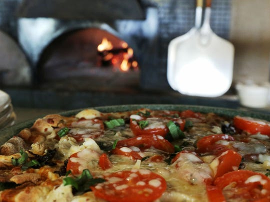 Pizza cools after baking in the brick oven at the Cosi Cucina in Clive on Wednesday. The original owners of the popular restaurant are back at the helm after hearing of the previous owners' decision to sell the business.
