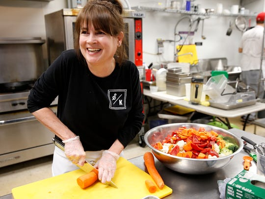 Kat Cahill, cuts vegetables at Saundra's Kitchen in