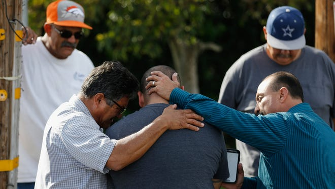 Men embrace in prayer near the  scene where suspects in the shooting at the Inland Resource Center were killed  Dec. 3, 2015, in San Bernardino, Calif.