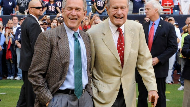 FILE - This Oct. 25, 2009 file photo shows former Presidents George H. W. Bush, right, and George W. Bush before the Houston Texans NFL football game against the San Francisco 49ers in Houston. George H. W. Bush and George W. Bush are cooperating with a historian for a joint biography about the former presidents. ìPresidents Bush: A Portrait of a Father and Son,î by Mark K. Updegrove, has been acquired by Henry Holt and Company. The book is scheduled for Spring 2016. (AP Photo/Dave Einsel, File) ORG XMIT: NYET208
