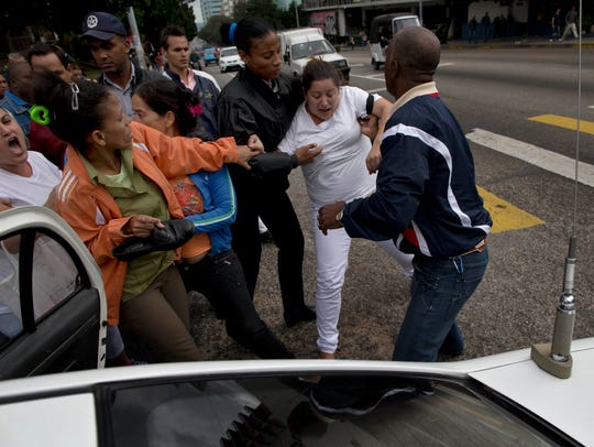 An opposition activist is detained by Cuban security