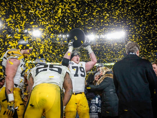 Iowa senior guard Sean Welsh raises the 2017 Pinstripe Bowl trophy as Hawkeye colored confetti flies after Iowa's 27-20 win over Boston College during the 2017 Pinstripe Bowl at Yankee Stadium in Bronx, New York on Wednesday, Dec. 27, 2017.