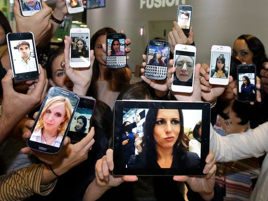 Television host Alicia Menendez, center, foreground, holds up a selfie with her production team as they pose for a photograph on Oct. 14 in Doral, Fla. The selfie is Oxford Dictionaries' word of the year for 2013.