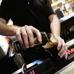 Scott Roberts, manager of The Pompei Lounge, pours a beer for a patron at the bar on Wednesday evening.