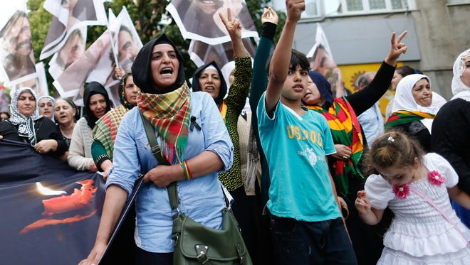 Protesters shout slogans against the Turkish government as they hold pictures of victims of the explosion in Suruc during a funeral ceremony in Istanbul, Turkey, 22 July 2015.  At least 32 people were killed and some 100 wounded in a suicide blast ouside a cultural centre in Suruc, Sanliurfa province 20 July 2015.
