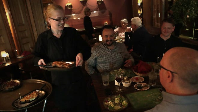 Lisa Scanlan, a server at George's Steak House in Appleton, brings a steak to Tom Carle of Appleton. He was dining at George's Wednesday with Fil Meraz of Silt, Colo., Justin Duchscher of New Castle, Colo., and Jonah Frank of New Castle, Colo.