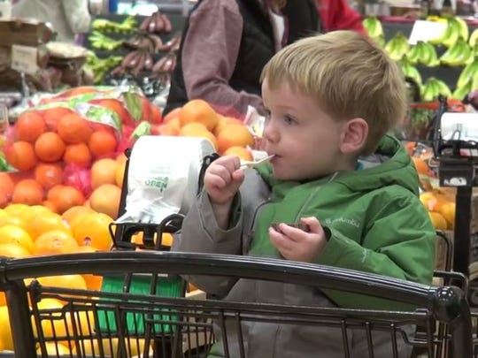 Patrick Lia, 2, of Webster, tucks into a sample during a celebration of the finished remodel at the Holt Road Wegmans.