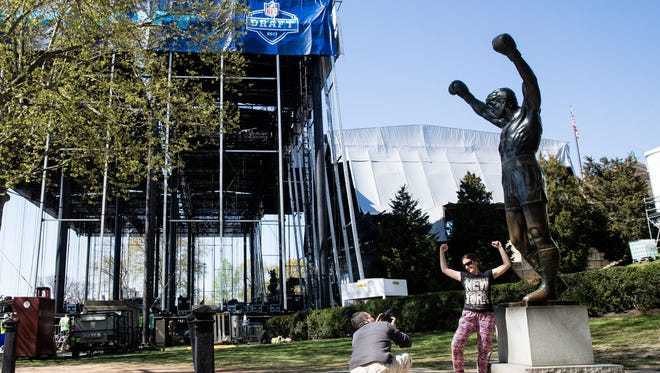 Tourist take photos with the Rocky statue as workmen construct the stage for the upcoming 2017 NFL football draft on the steps of the Philadelphia Museum of Art in Philadelphia, Tuesday, April 18, 2017. When the NFL chose Philadelphia to host the 2017 draft, they insisted on holding the three-day event at the Art Museum in front of the iconic Rocky steps. Mayor Jim Kenney and city officials made it happen so construction crews are putting together a 3,000-seat theater for an extravaganza that's expected to draw about 200,000 people to the venue. (AP Photo/Matt Rourke)