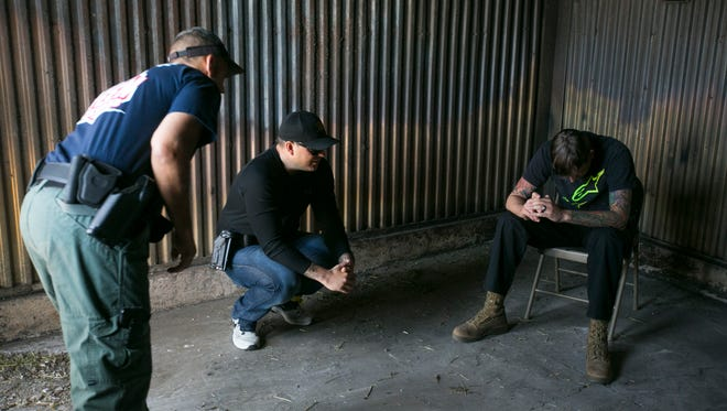 Scottsdale police officers Fred Pera (L) and officer Mike Hertko (center) respond to ASU social work student James Gray during crisis intervention training at the police training center in Tempe on April 10, 2015.
