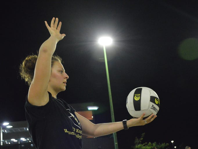 A student prepares to serve the ball during the third