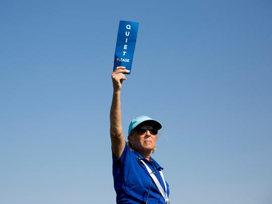 """A volunteer holds up a """"quiet"""" sign during the CME Group Tour Championship at Tiburon Golf Club Thursday, Nov. 17, 2016 in Naples."""