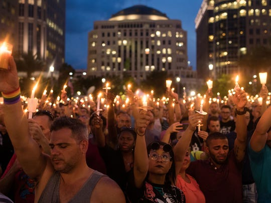 File photo taken in June 2016 shows people hold candles during a ceremony in Orlando, Florida for victims of the Pulse Nightclub shootings.