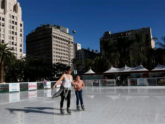 Parts of California have set records with highs topping 80 degrees in the dead of winter. Andrea Davis and her daughter Luna Rivera, 10, enjoy the best of both worlds, ice skating at the Holiday Ice Rink in downtown Los Angeles on Tuesday, Jan. 6, 2015.