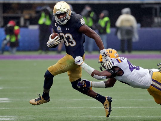 Notre Dame running back Josh Adams (33) makes a move to escape a tackle by LSU linebacker Michael Divinity Jr. during the second half of the Citrus Bowl NCAA college football game, Monday, Jan. 1, 2018, in Orlando, Fla. Notre Dame won 21-17. (AP Photo/John Raoux)