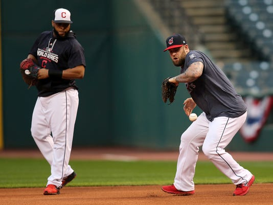 Cleveland Indians' Mike Napoli, right, fields a ball as Carlos Santana looks on during a team practice for baseball's upcoming World Series against the Chicag Cubs, Sunday, Oct. 23, 2016, in Cleveland. (AP Photo/Aaron Josefczyk)