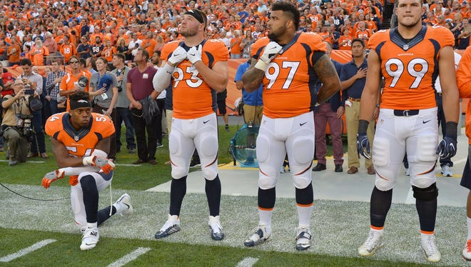 Brandon Marshall takes a knee during the national anthem before Denver's win over Carolina.
