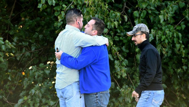 Unidentified bystanders embrace as police and Emergency Medical Services respond to a shooting at a business park in the Edgewood area of Harford County, Md., Wednesday, Oct. 8, 2017.
