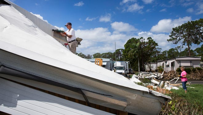 Reid Fretz cuts his ruined aluminum roof into smaller pieces as he and his wife, Trudy, clean up their trailer at Imperial Bonita Estates in Bonita Springs on Wednesday, Oct. 04, 2017.