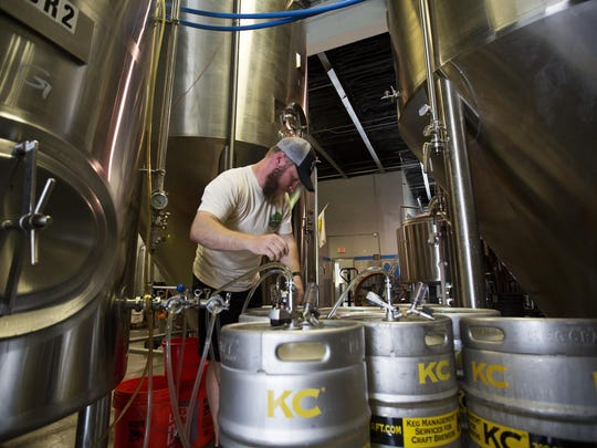 KJ Lynch, the head brewer at Fort Myers Breweries dispenses Gateway Gold beer into kegs on Monday 6/29/2015. Starting July 1, 64 ounce growlers of beer will be for sale throughout the state.