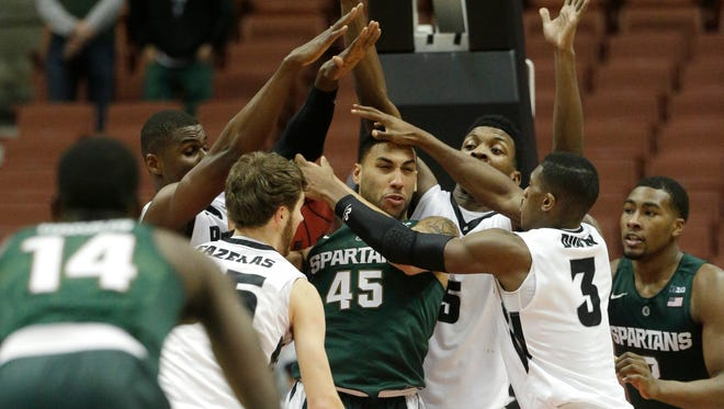Denzel Valentine tries to escape a pack of Providence players Sunday night.