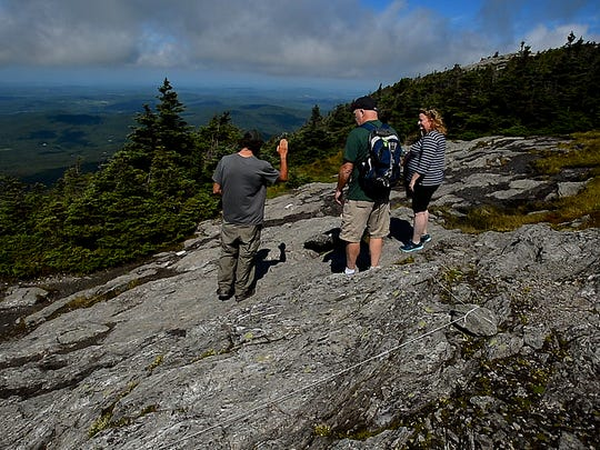 Adam Joseph, Mount Mansfield lead with the Green Mountain Club, talks to day hikers new to the Vermont peak, asking them to stick to the trail, but more importantly to only step on hard rock and avoid stepping on plants and soil or gravel deposits where plants can grow, even if they are in the 'trail'.