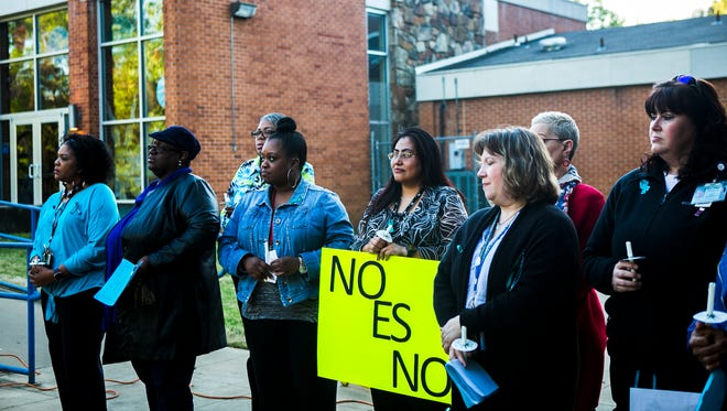 "April 7, 2017 - Guadalupe Altamirano-Gutierrez, an employee with Shelby County Crime Victims Center, holds a sign stating ""No Es No"" or ""No Is No"" as she stands with fellow advocates during the Shelby County Rape Crisis Center Candlelight Vigil at Peabody Park on Friday evening."