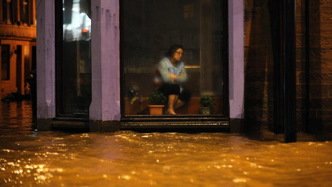 A woman sits inside a Chinese Restaurant watching flood water race by the window in Dumfries, southern Scotland, on December 30, 2015 after heavy rainfall brought by Storm Frank.