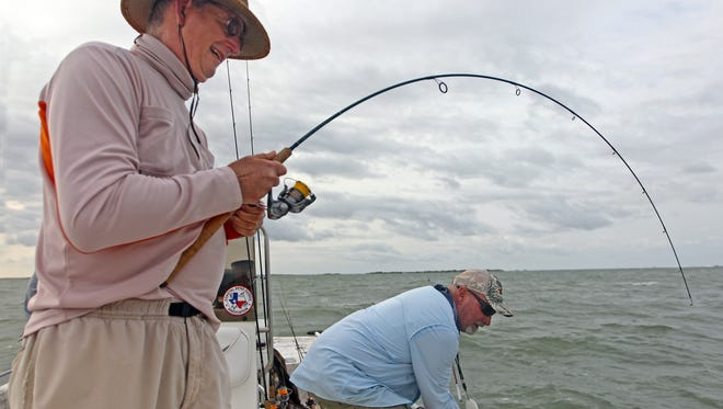 Notice the bend in Bill Cash's fishing rod and the grin on his face.