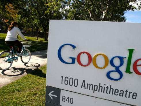 A Google employee rides a bicycle by a sign at the company's headquarters in Mountain View, Calif.