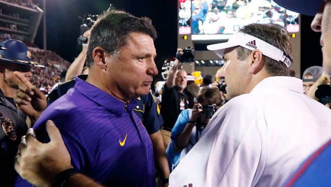 Mississippi State head football coach Dan Mullen confers with LSU head football coach Ed Orgeron following their NCAA college football game against in Starkville, Miss., Saturday, Sept. 16, 2017. Mississippi State won 37-7.