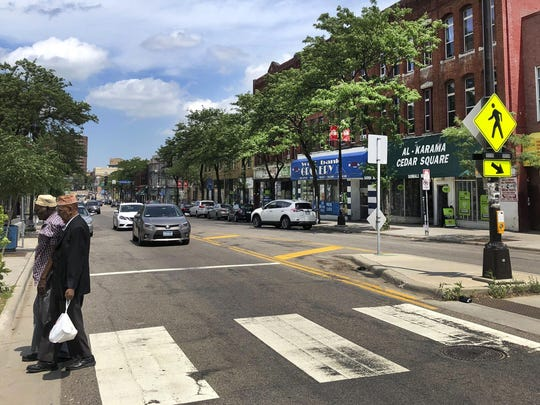 Two men walk across the street in Minneapolis' Cedar-Riverside neighborhood, part of the congressional district represented by Democrat Ilhan Omar, Monday, July 15, 2019, in Minneapolis. The neighborhood, tucked between downtown Minneapolis and the University of Minnesota, is home to many of the city's large population of Somali-Americans. (AP Photos/Doug Glass)