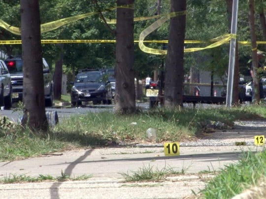 A line of evidence markers follow a trail of blood down Central Avenue in Asbury Park Thursday as police continue their investigation of a multiple shooting there.