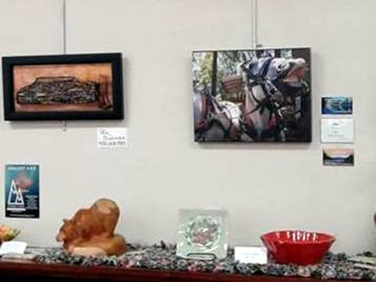 Photographs, wood carving, pottery and many more mediums are represented in the Alto Studio Tour advance exhibits at Ruidoso and Capitan libraries. This shows a table of work in Capitan.