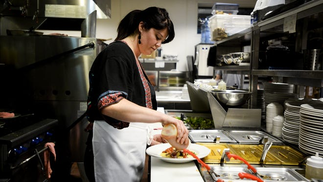 Amelia Mouton prepares a dish in the kitchen of Restaurant 415.