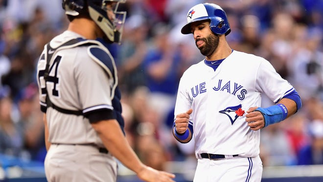 Toronto Blue Jays' Jose Bautista (19) scores on a sacrifice fly by Justin Smoak as New York Yankees catcher Gary Sanchez (24) waits during the third inning of a baseball game Friday, June 2, 2017, in Toronto.