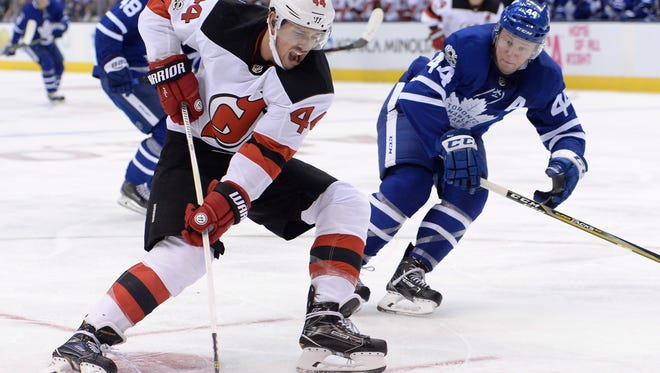 New Jersey Devils left wing Miles Wood (44) drives to the net past Toronto Maple Leafs defenseman Morgan Rielly (44) during the third period of an NHL hockey game Wednesday, Oct. 11, 2017, in Toronto. (Nathan Denette/The Canadian Press via AP)