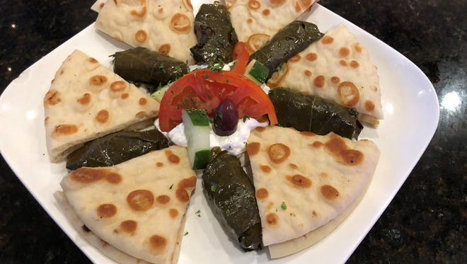 Dolmadaki, stuffed grape leaves filled with seasoned rice, served with tzatziki sauce and grilled pita bread at Olympia Dining, Naples.